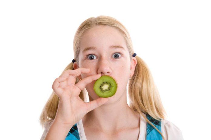 Young girl holding half a kiwifruit